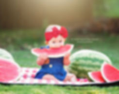 baby girl in overalls eating watermelon professional photography