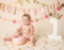 baby girl smashing first birthday cake photography session photo shoot with cream gold and pink colors