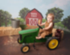 baby sitting on john deere tractor with whimsical farm barn backdrop photography