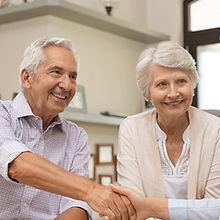 Happy senior couple sealing with handsha