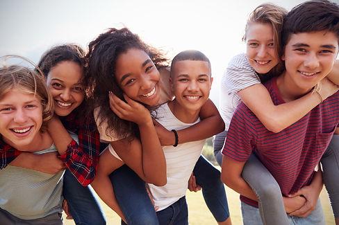 Teenage school friends having fun piggyb