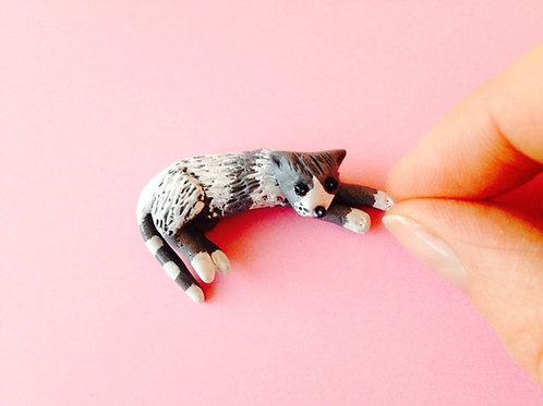 Chat miniature, en pâte polymère. Allongé, pattes devant, gris et blanc