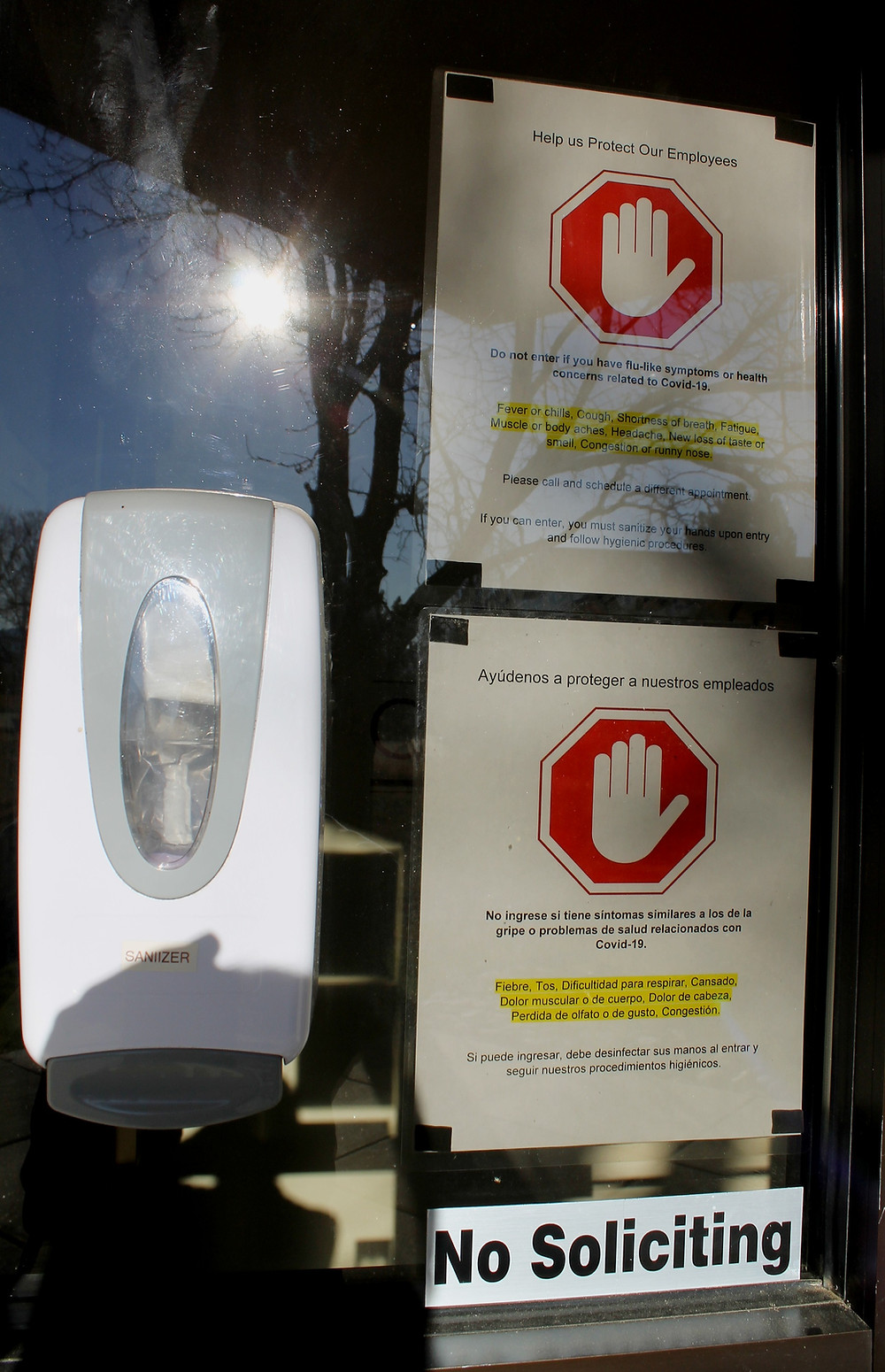 A picture showing a hand sanitizer dispenser and several warning signs discussing COVID-19 guidelines at the front door of the Claremont office.