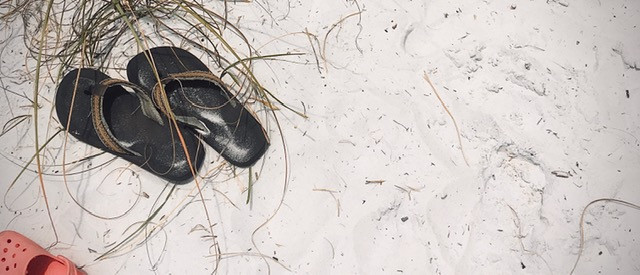 Empty sandals lying in soft white sand on a Florida beach
