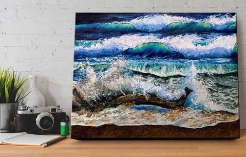 Original oil painting of surf crashing over driftwood on an empty beach, sitting on a wood desk in a home office