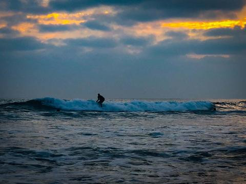 Surfer riding a wave while silhouetted against a sunset sky over the ocean