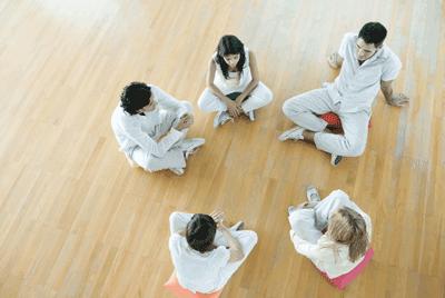 Gruppe sitzt bei einer systemischen Familientherapie