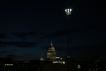 A moonlight tower in front of the Texas capitol