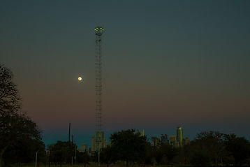 A moonlight tower with the moon in the background