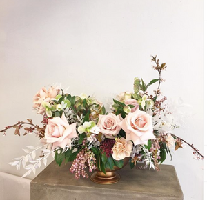 Blush pink roses in a wedding centrepiece on a table with a neutral background