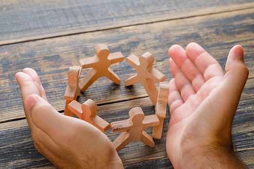 business-success-concept-wooden-table-top-view-hands-protecting-wooden-figures-people (1).