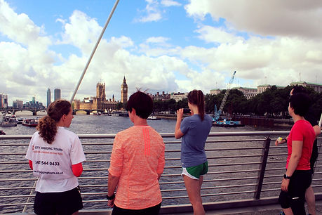 Running tour guide with guests enjoyig the views across the River Thames, looking towards the Houses of Parliament