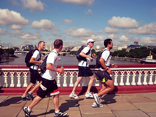Runners jogging over Blackfriars bridge with London skyline in the background