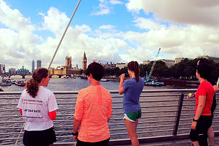 Running tour guide with guests admiring the views across the Thames from the Golden Jubilee footridge in London