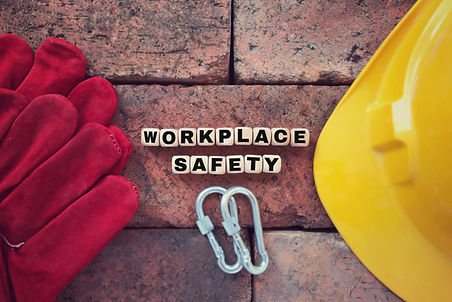 """Brick wall background with Red Gloves and Yellow Hard hat with words """"Workplace Safety"""" between them"""