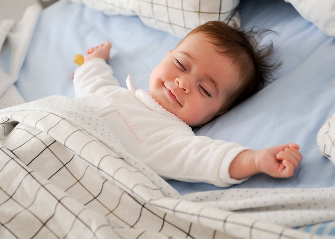 smiling-baby-lying-on-a-bed.jpg