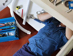 Handyman wearing blue coveralls works underneath a kitchen sink. There is a toolbox next to him.