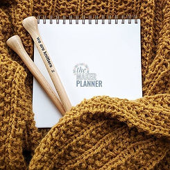 The Maker Planner crochet and knit planner journal tracker laying on top of a knit sweater and knitting needles