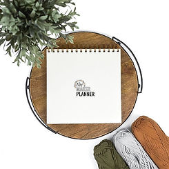 The Maker Planner crochet and knit planner journal tracker with skeins of yarn and a plant