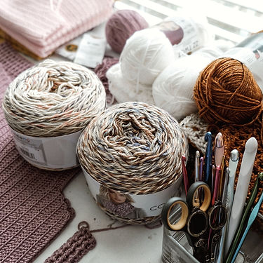 Various skeins of different colored yarn and crochet hooks