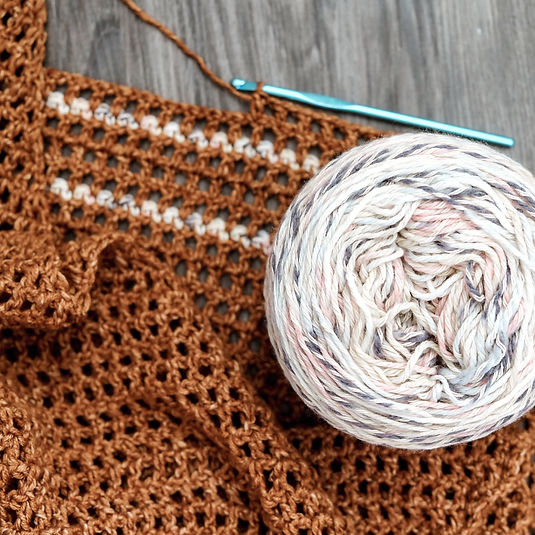 A skein, ball, or cake of yarn close up and detailed sitting on top of a crocheted project