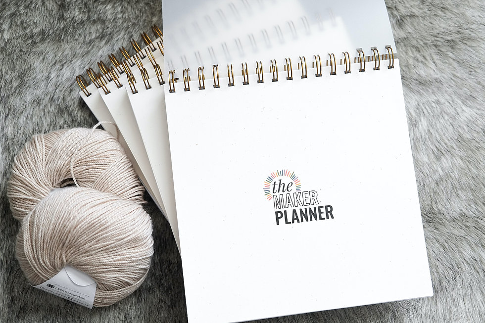 A stack of The Maker Planner crochet and knit planners journals trackers