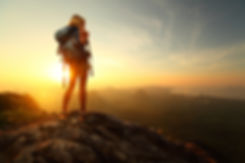 Hiker with backpack relaxing on top of a