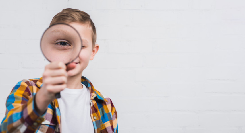 close-up-boy-looking-through-magnifying-