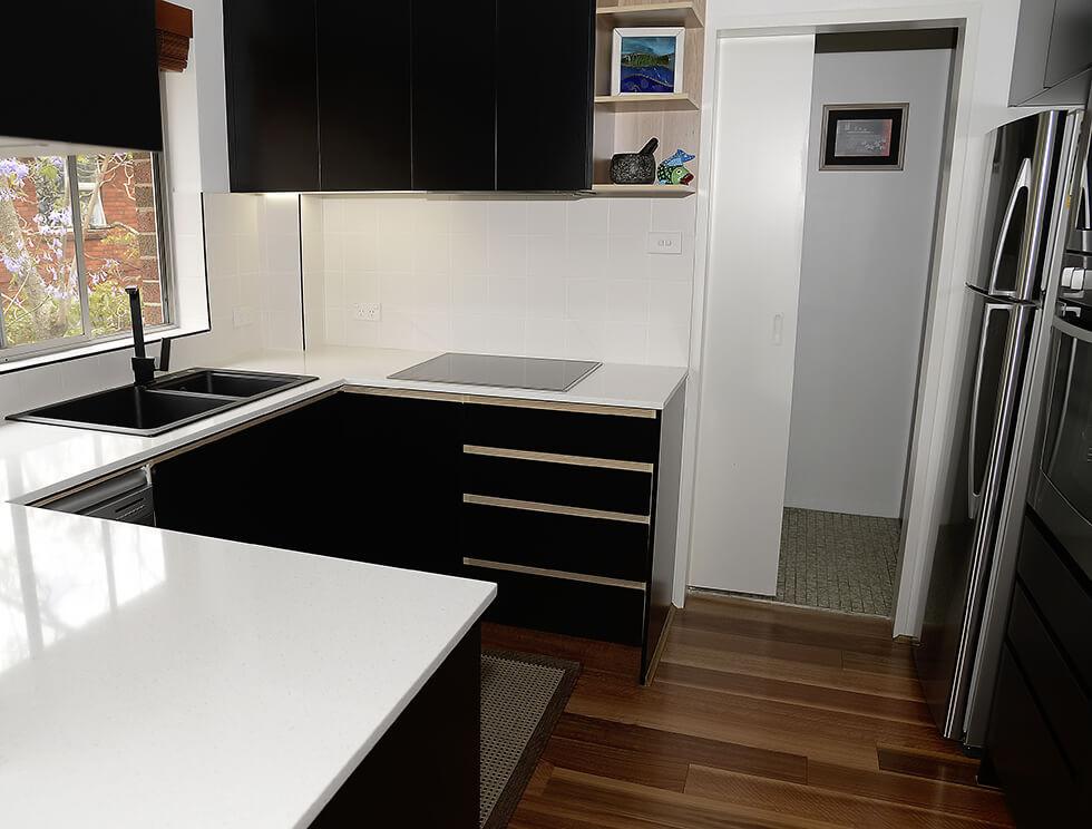 Black laminate finish, contrast timber handle grip , Silestone bench top.