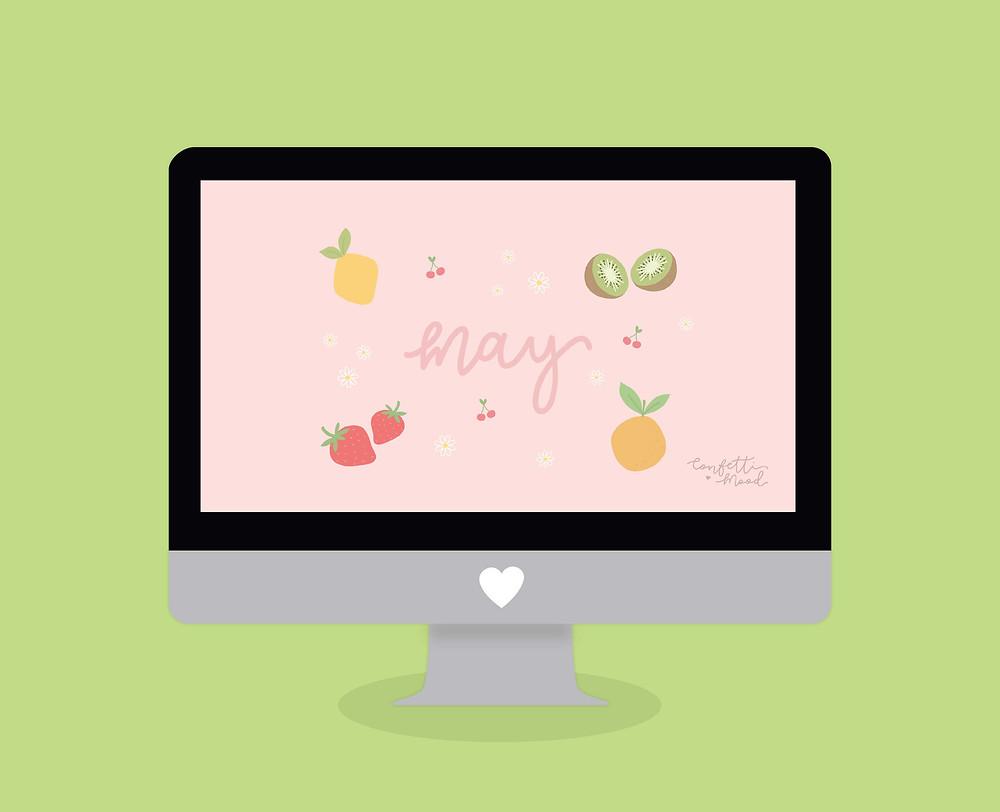 """Immagine dello sfondo per computer di Maggio. L'illustrazione rappresenta un computer con il desktop di Maggio Confetti Mood. Lo sfondo ha al centro la scritta """"may"""" in corsivo, circondata da frutta di stagione come limone, arancia, kiwi, fragola e ciliege."""