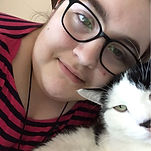 A white girl with hazel eyes and hipster glasses smiles slightly while attempting to take a selfie with her black and white cat, who is looking slightly to the left of the camera and seems relaxed.