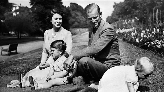 Queen Elizabeth II & Philip, captured informally with their two children in 1952 -  (left) Prince Charles, The Duke of Cornwall and (right) Princess Anne ​