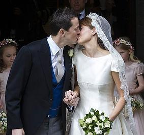 Thomas & Alexandra, sharing a kiss following their wedding at Romsey Abbey 