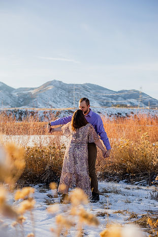 couple kissing and holding hands in the snow in front of colorado mountains at waterton canyon