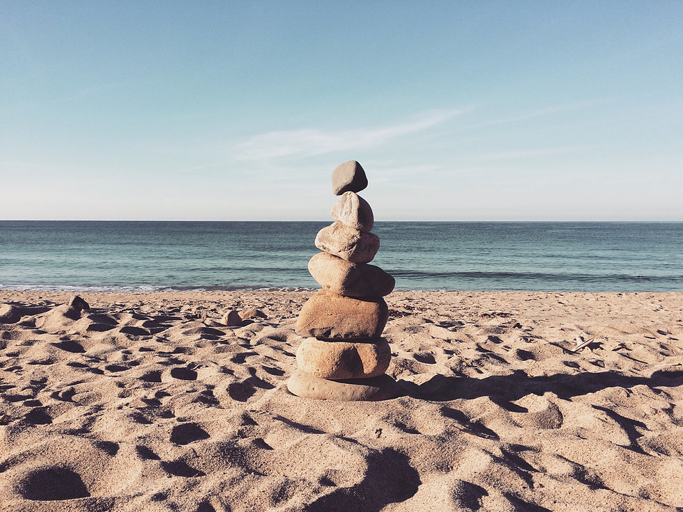 Stack of pebbles on a beach with sea in the backgroun