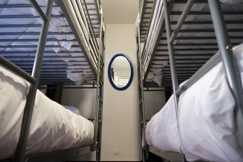 Beliches e espelho de quarto partilhado no Help Yourself Hostels Restelo