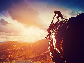 Hikers climbing on rock, mountain at sun