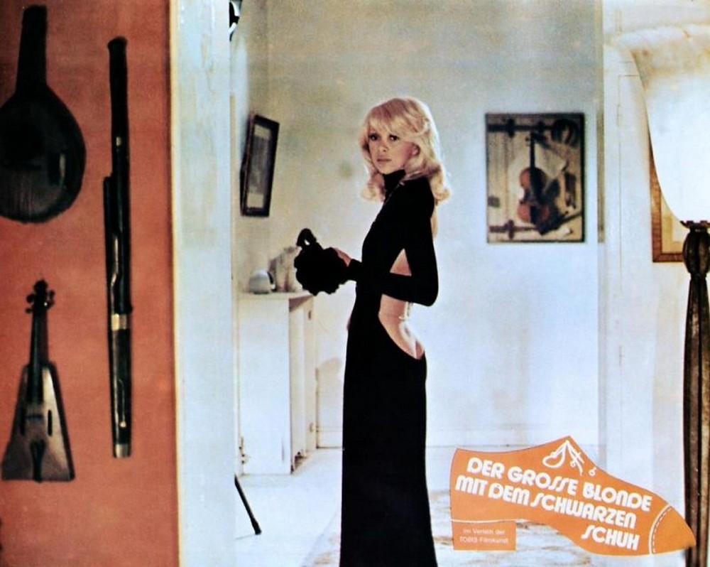 Mireille Darc porte une robe très échancrée dans Le grand blond avec une chaussure noire