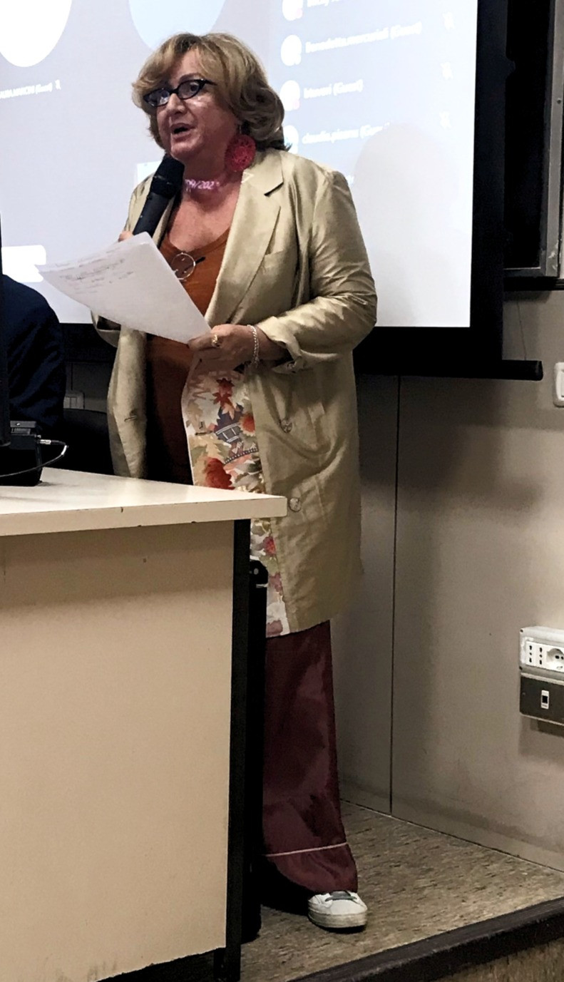 A woman holding a microphone and a script stands in front of a projector to address the audience