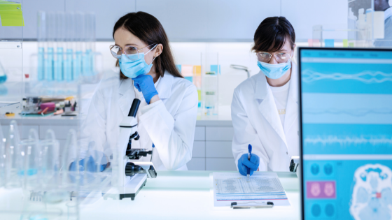 An image of two female scientists in a laboratory, working with a microscope and a brain scan
