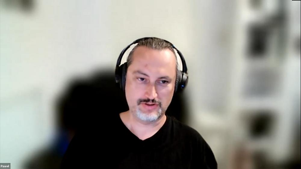 Dr Paweł Boguszewski, speaks on video call with headphones
