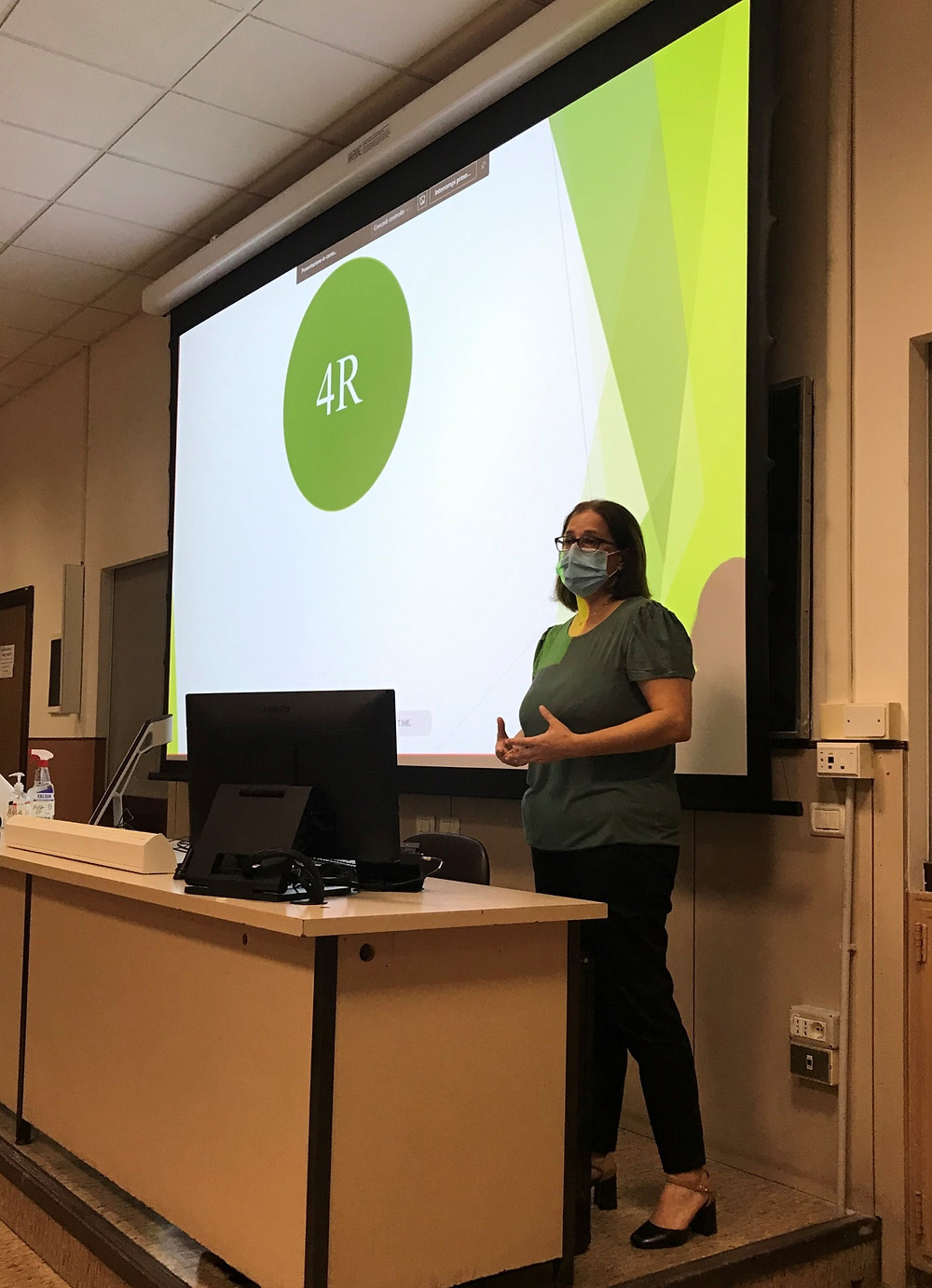 """A woman stands in front of a projector displaying a PowerPoint slide with green writing saying """"4Rs"""""""
