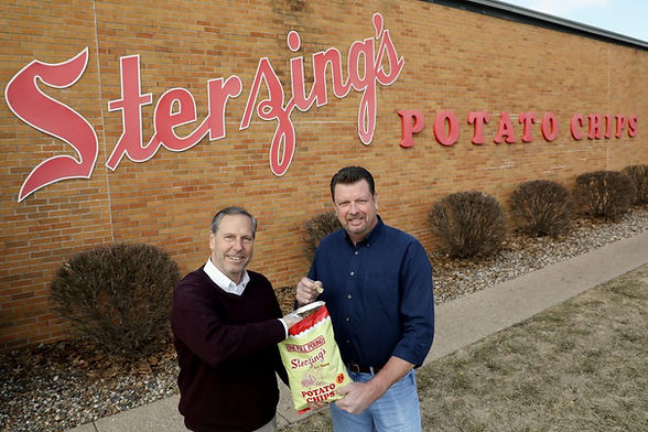 Owners Craig and Gary Holding Sterzing's Potato Chips in front of office building.