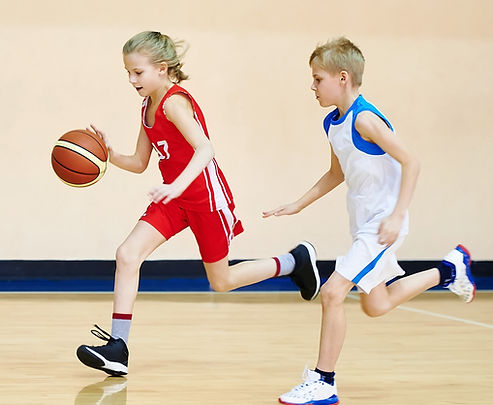 Girl and boy athlete in sport uniform playing basketball.jpg