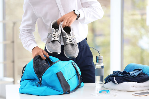 Young businessman packing sports stuff f