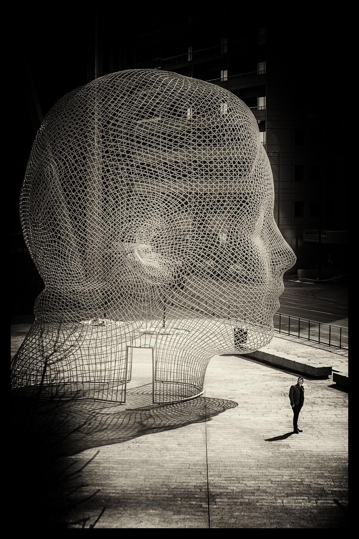 A man walks by the big head.