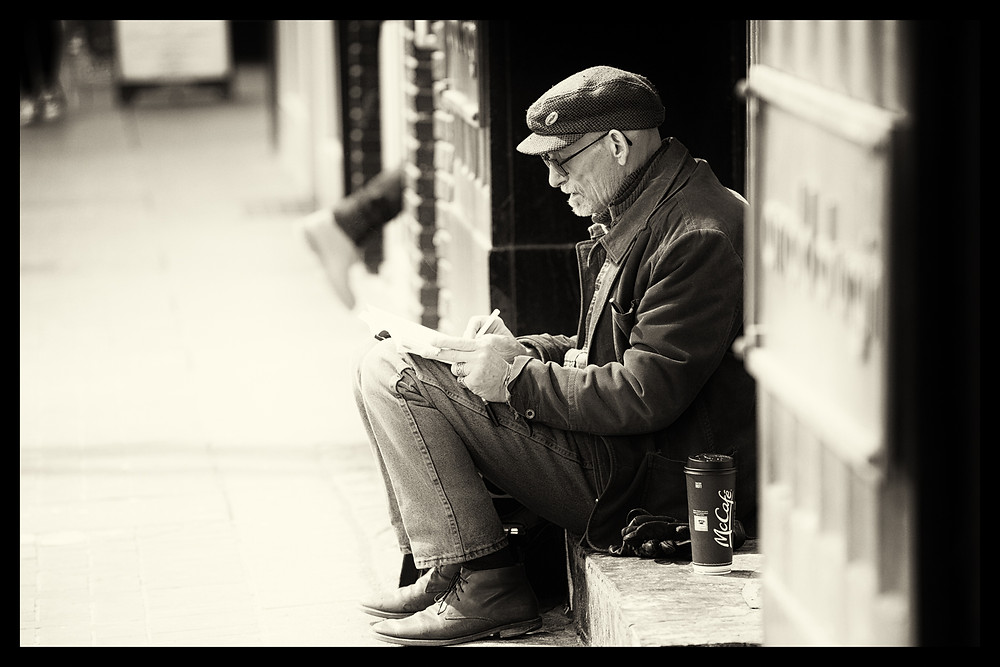 An older gentleman sits in the sun with his coffee and crossword.