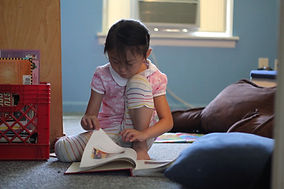 Girl reads book on the carpet