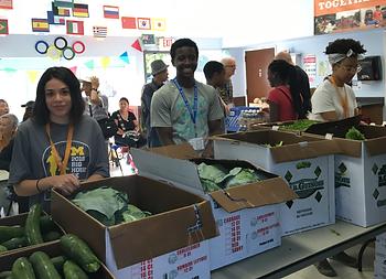 Teen smiles while volunteering at food distribution