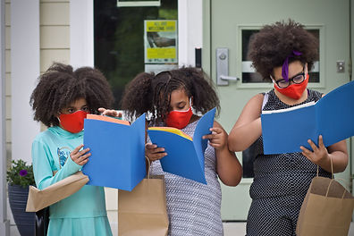 Students with masks look through folders